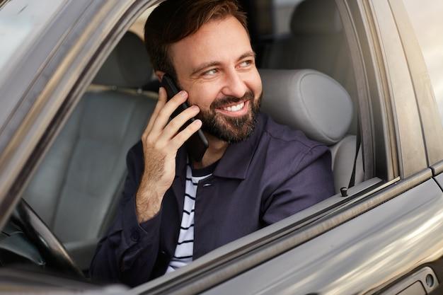 Il giovane uomo barbuto riuscito attraente felice si siede sulla macchina e parla al telefono con il suo amico, sorridendo ampiamente e distogliendo lo sguardo. Foto Gratuite