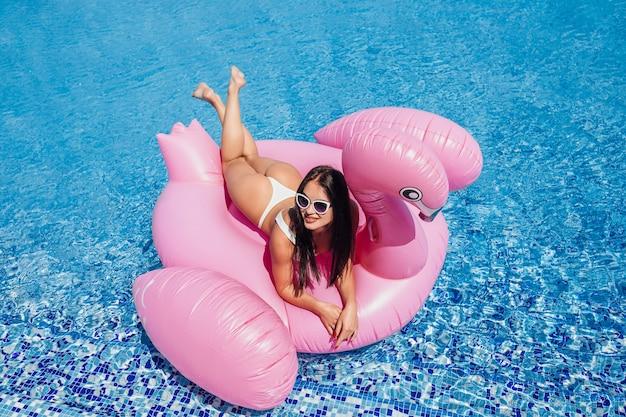 Молодая счастливая красивая женщина брюнет с красивой фигурой, загорая на надувном фламинго в бассейне. Premium Фотографии