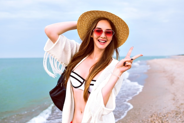 Young happy blonde girl posing on the beach, wearing straw hat and heart cute sunglasses, enjoy her summer vacation near ocean, wearing bikini and boho jacket. Free Photo