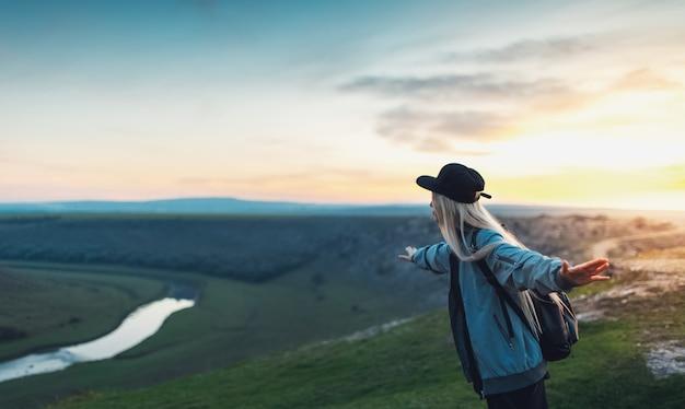 Молодая счастливая блондинка с черным рюкзаком и кепкой, взявшись за руки, как самолет на пике холмов на закате. концепция путешествия. Premium Фотографии