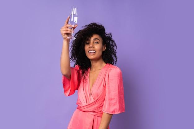 Giovane donna brasiliana felice con capelli ricci in abito elegante rosa in posa con un bicchiere di champagne sopra la parete viola. atmosfera di festa. Foto Gratuite