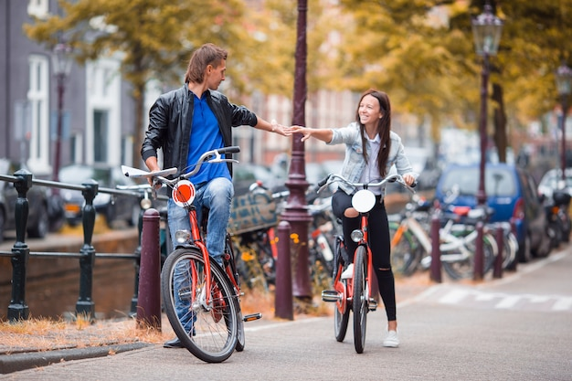 Young happy caucasian couple on bikes in old streets in amsterdam Premium Photo