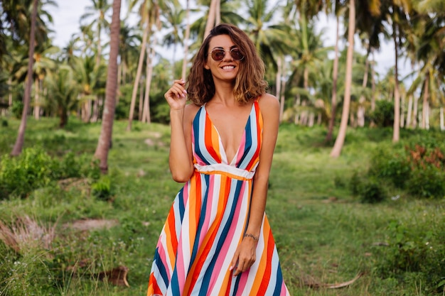 Free Photo Young Happy Caucasian Woman In Colorful Striped Summer Dress With Short Curly Hair In Sunglasses Vacation In Warm Exotic Country