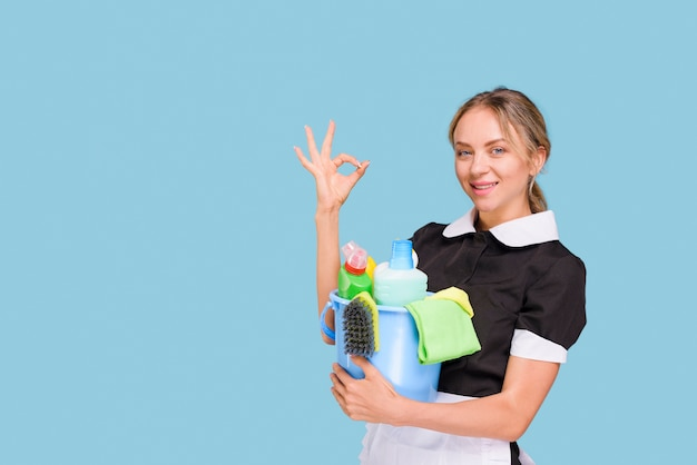Young happy cleaner woman showing ok sign holding bucket of cleaning products over blue surface Free Photo