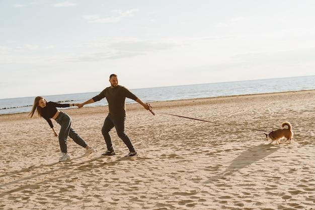 若い幸せなカップルとビーチの上を歩く犬。 Premium写真