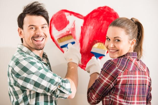 Молодая счастливая пара красит сердце на стене. Premium Фотографии