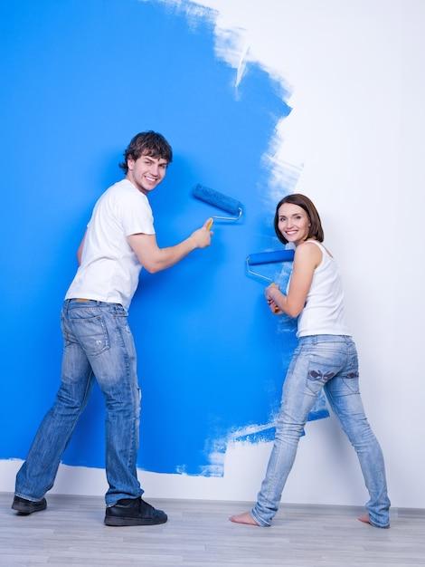Giovani coppie felici in casuals spazzolando il muro Foto Gratuite