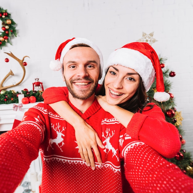 Young happy couple embracing in christmas hats Free Photo