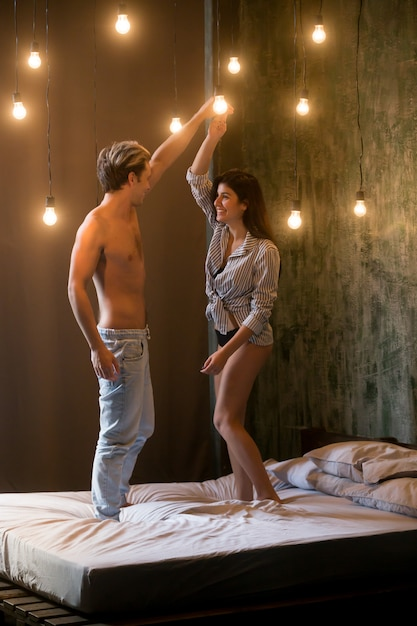 Young happy couple having fun dancing together standing on bed Free Photo