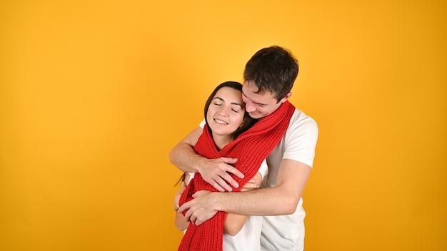 Молодая счастливая пара обнимает друг друга на желтом Premium Фотографии