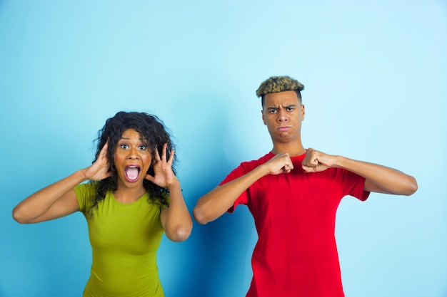 파란색 벽에 포즈 캐주얼 옷에 젊은 행복 한 커플 무료 사진