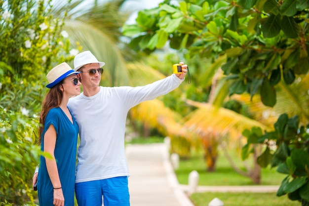 Young happy couple making selfie with mobile phone on tropical vacation Premium Photo