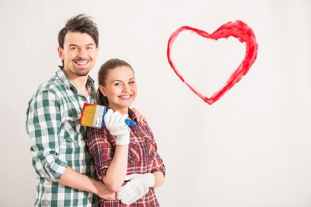 Молодая счастливая пара нарисовала сердце на стене. Premium Фотографии