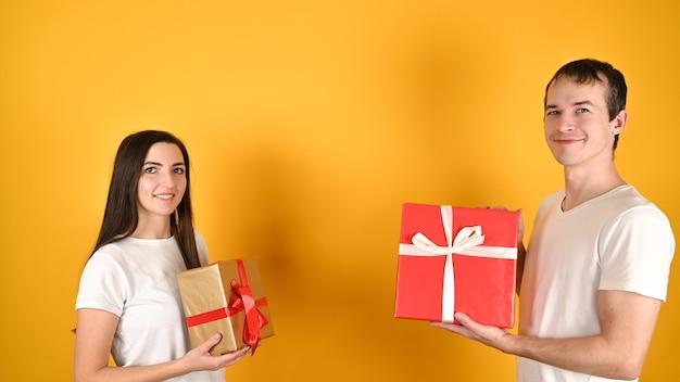 Молодая счастливая пара получила подарки друг от друга на желтом Premium Фотографии