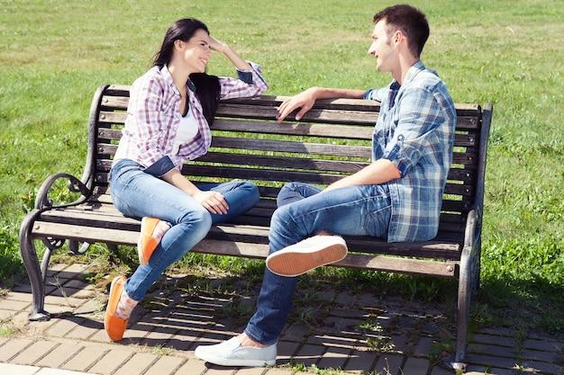 公園のベンチで休んで座っている若い幸せなカップル Premium写真