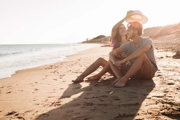 Young happy couple sitting next to the sea Free Photo