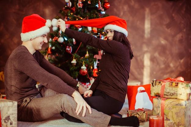 スタジオでサンタの帽子を着ている若い幸せな夫婦 無料写真