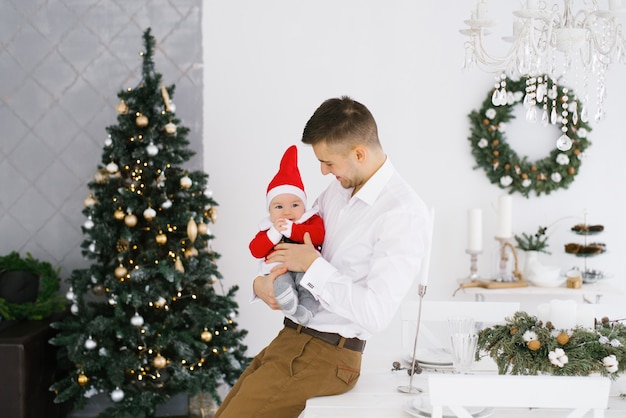 Young happy dad holding his little son in santa costume near christmas tree in living room Premium Photo