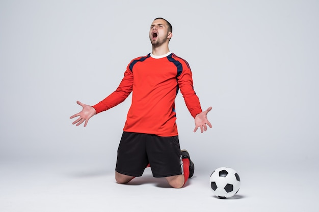 Young happy and excited football player in red jersey celebrating scoring goal Free Photo
