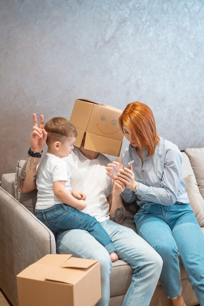 Young happy family with kid unpacking boxes together sitting on sofa Free Photo