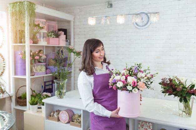 Young happy florist making fresh flowers arrangement in gift box Premium Photo