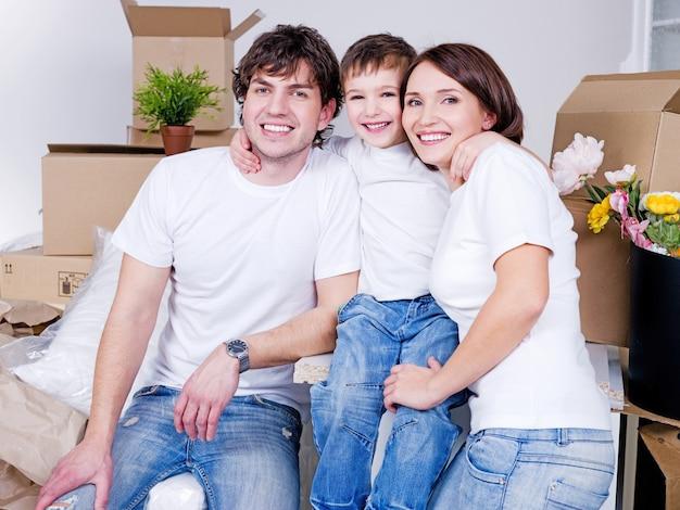 Giovane famiglia amichevole felice che si siedono insieme nel loro nuovo appartamento Foto Gratuite
