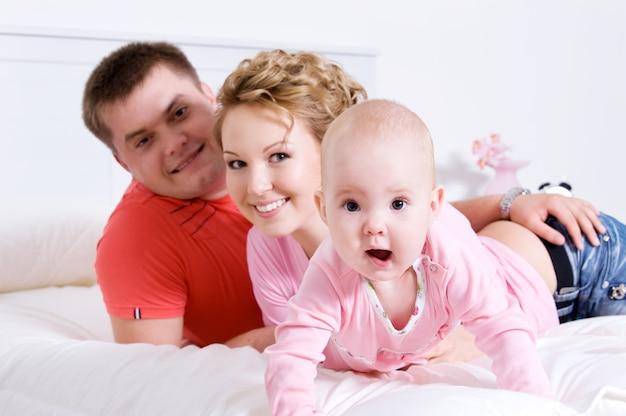 Молодая счастливая веселая семья с ребенком, лежащим на кровати у себя дома Бесплатные Фотографии