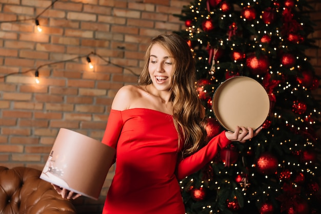Young happy girl holding gift box in hands.new year present, winter shopping Premium Photo