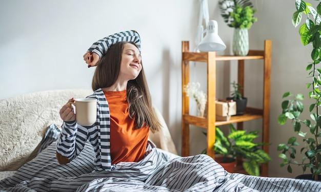 Молодая счастливая девушка в пижаме сидит в постели с чашкой ароматного кофе и потягивается после пробуждения Premium Фотографии