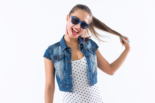 Молодая счастливая девушка смеется, держа ее за волосы, имитируя прически хвосты, носить солнцезащитные очки и модный наряд. Premium Фотографии