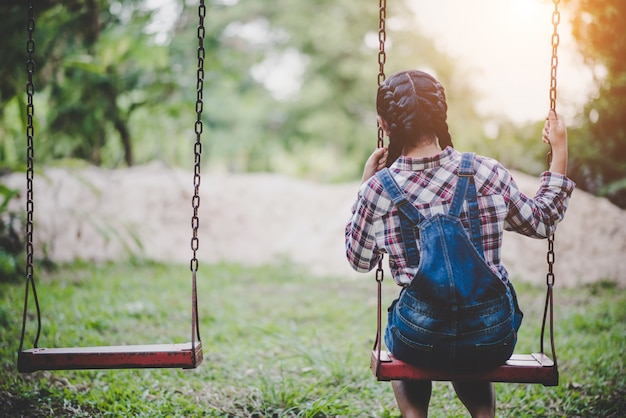 Young happy girl riding on a swing in the park Free Photo