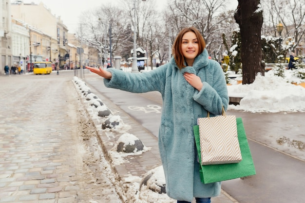 Young happy girl with shopping bags catch a taxi. Free Photo