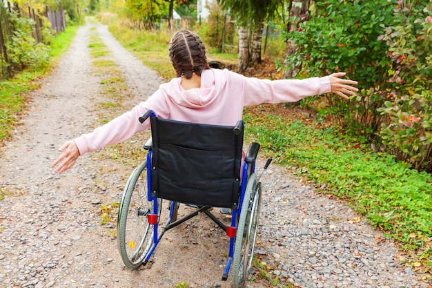 Premium Photo   Young happy handicap woman in wheelchair on road in  hospital park enjoying freedom. paralyzed girl in invalid chair for  disabled people outdoor in nature. rehabilitation concept.