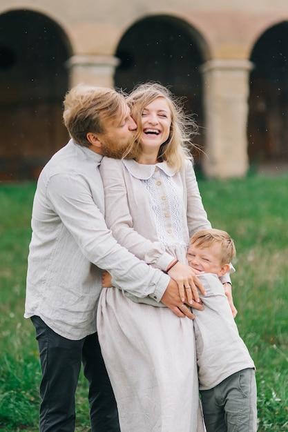 雨の中で抱き締める若い幸せな愛情のある家族。雨滴の子供と一緒にリネンの衣装を着た本物の家族 Premium写真