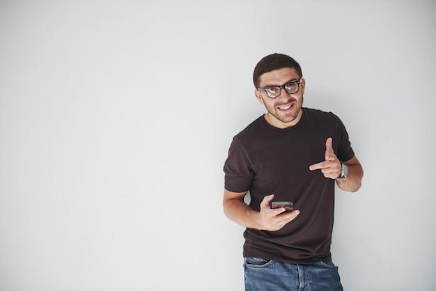 白のスマートフォンを着てカジュアルな若い幸せな男 無料写真