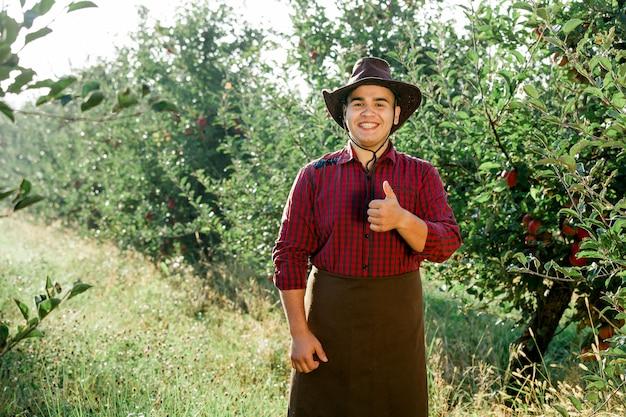 Молодой счастливый человек в саду собирать спелые яблоки Premium Фотографии