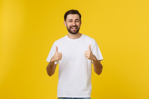 Young happy man with thumbs up sign in casuals isolated on yellow Premium Photo