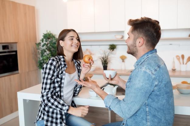 Giovane uomo felice e donna in cucina facendo colazione, coppia insieme al mattino, sorridendo, parlando Foto Gratuite