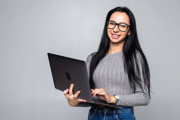 Молодая счастливая усмехаясь женщина в вскользь одеждах держа компьтер-книжку изолированный на серой стене Бесплатные Фотографии