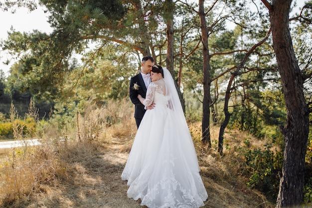 Giovani sposi felici. abbraccio caucasico dello sposo e della sposa Foto Gratuite