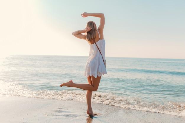 Молодая счастливая женщина танцует, поворачиваясь на берегу моря в солнечном летнем стиле моды в белом платье на каникулах Бесплатные Фотографии