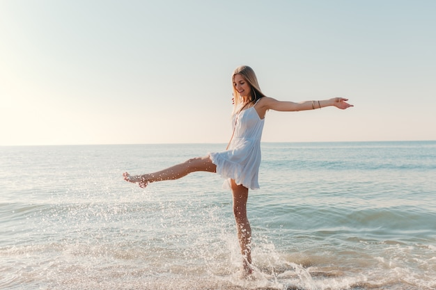 Young happy woman dancing turning around by sea beach sunny summer fashion style in white dress vacation Free Photo