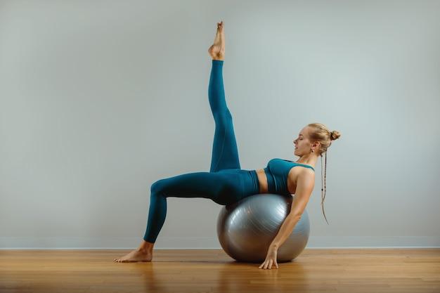 Молодая счастливая женщина делает фитнес-упражнения с подходящим мячом дома. Premium Фотографии
