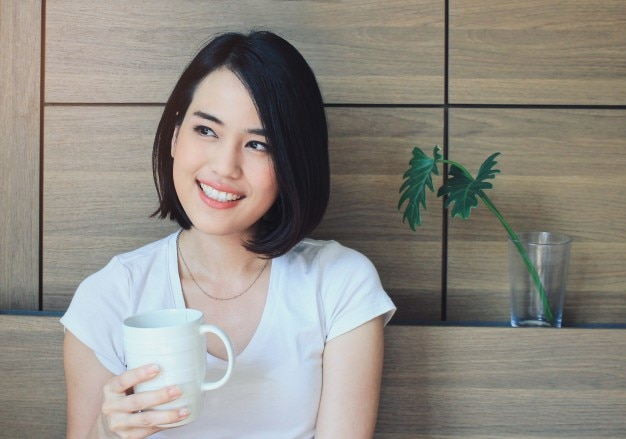 Young happy woman in casual clothes relaxing on bed while drinking tea or coffee, lifestyle and wellness concept Free Photo