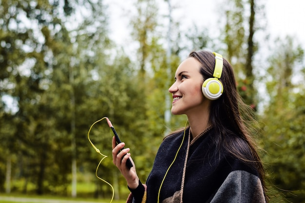 Young happy woman listening music from smartphone with headphones in a quiet park Premium Photo