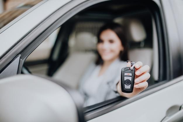 Giovane donna felice vicino alla macchina con le chiavi in mano. concetto di acquisto di auto. concentrati sulla chiave. Foto Gratuite