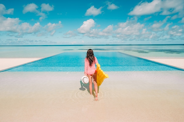 Young happy woman relaxing in a swimming pool Premium Photo