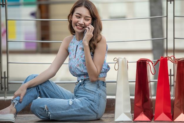 ショッピングバッグで床に座って、ショッピングモールでスマートフォンで話している若い幸せな女。 Premium写真