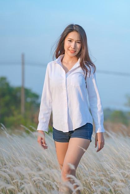 夕日の光の中でフィールドに立っている若い幸せな女性 Premium写真