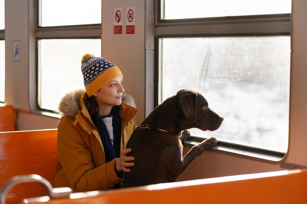 Young happy woman wear winter clothes sitting in local train with her lovely dog, hugging, thinking, looking through the window, traveling together. love pets. Premium Photo